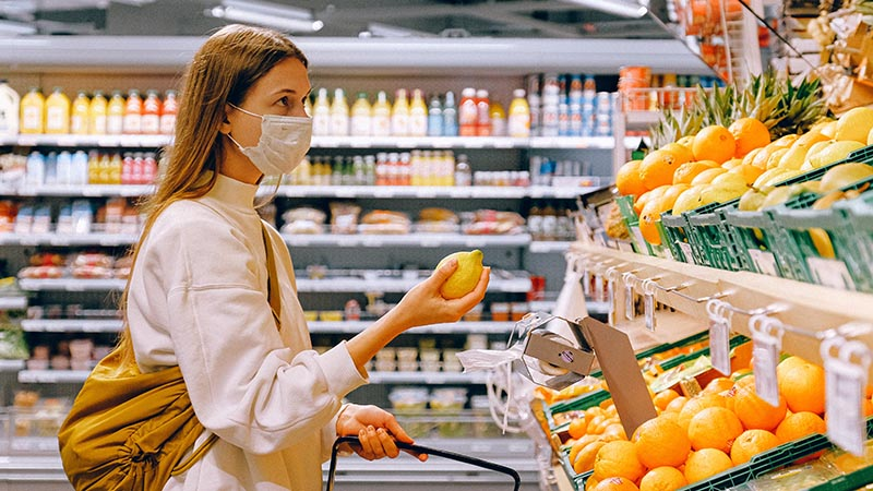woman wearing mask while produce shopping
